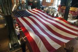 Visitors to Pittsburgh's Senator John Heinz History Center participate in a flag-folding ceremony in honor of Memorial Day on Monday, May 29, 2017 at the museum's grand hall in the Strip District. The 36 foot long flag weighs about 40 pounds.(Stephanie Strasburg/Pittsburgh Post-Gazette via AP)