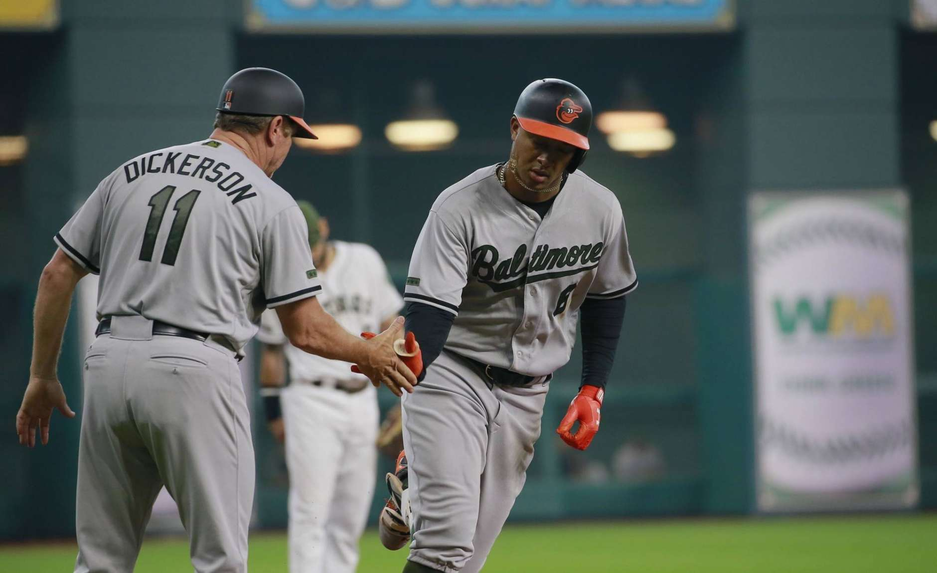 Baltimore Orioles' Jonathan Schoop is congratulated by third base coach Bobby Dickerson after his home run against the Houston Astros in the first inning of a baseball game Sunday, May 28, 2017 in Houston. (AP Photo/Richard Carson)