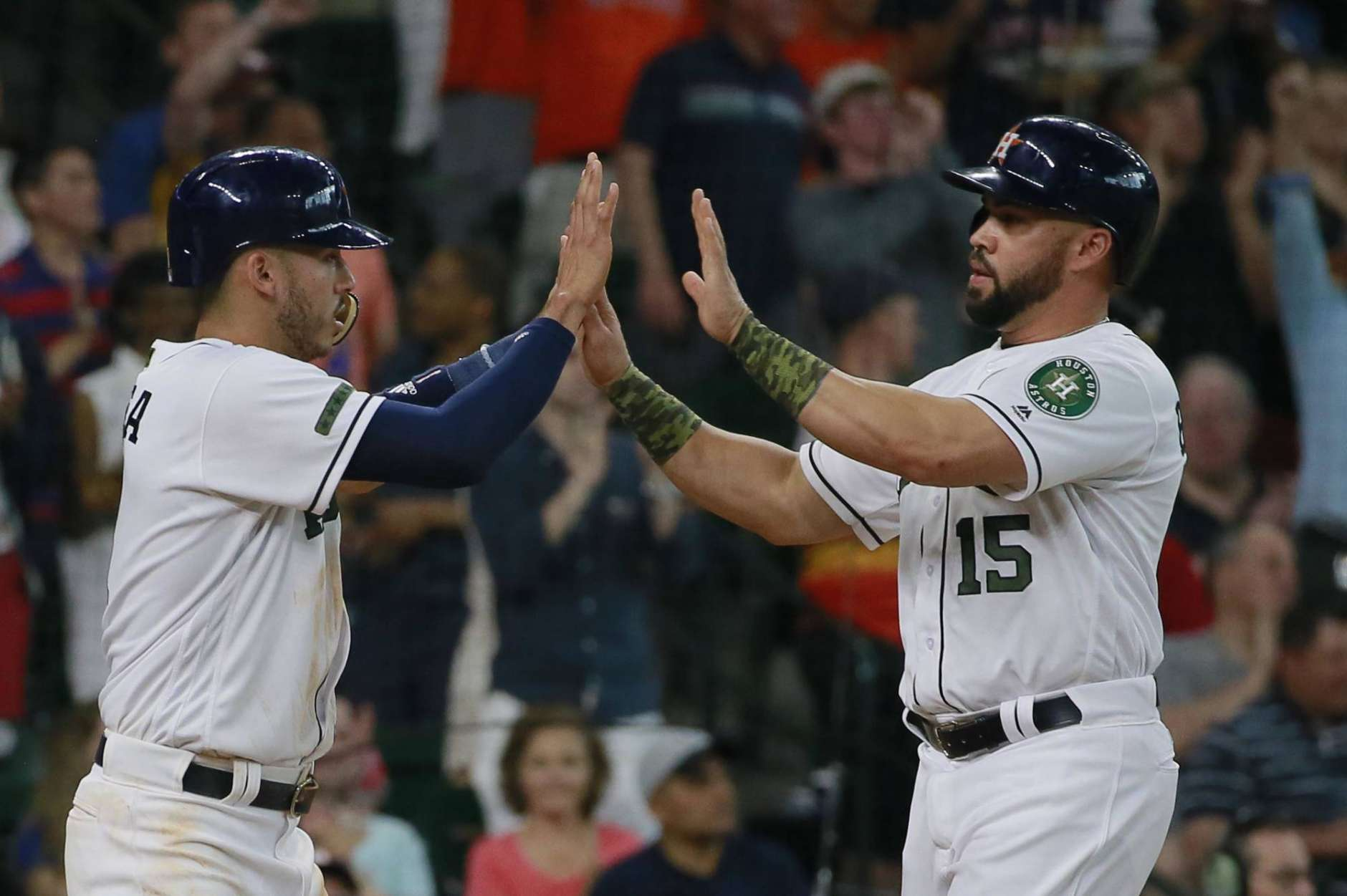 Houston Astros' Carlos Correa, left, greets teammate Carlos Beltran at home as the pair scored against the Baltimore Orioles in the second inning of a baseball game Sunday, May 28, 2017, in Houston. (AP Photo/Richard Carson)