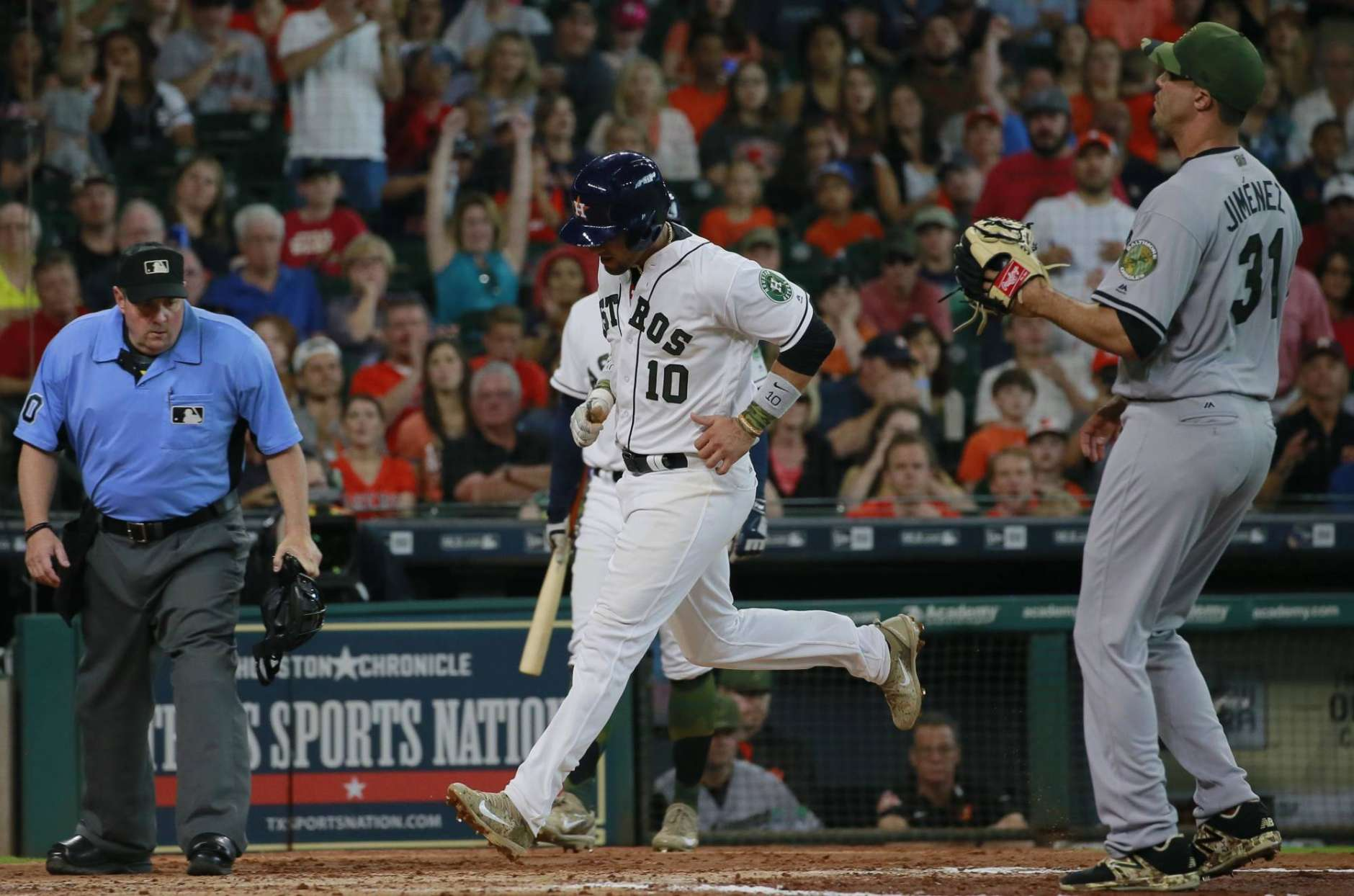 Houston Astros' Yuli Gurriel (10) scores on a wild pitch by Baltimore Orioles' reliever Ubaldo Jimenez (31) in the third inning of a baseball game Sunday, May 28, 2017, in Houston. (AP Photo/Richard Carson)