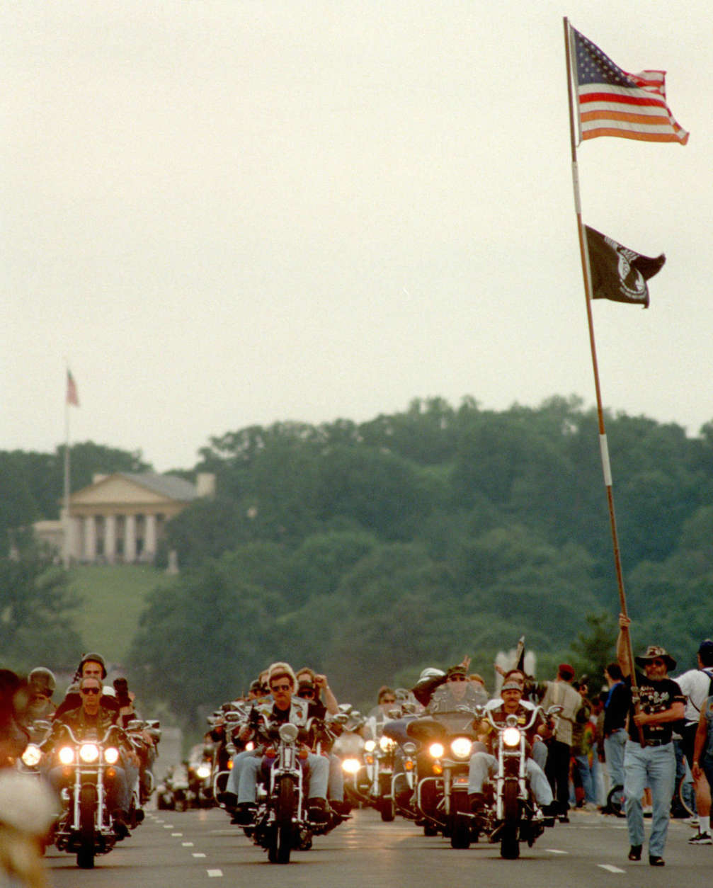 "American and POW/MIA flags fly as members of Rolling Thunder cross the Memorial Bridge riding from Virginia into Washington Sunday, May 24, 1998.  Bikers from around the world converged in Washington for the 11th Annual Memorial Weekend ""Rolling Thunder"" Rally to protest what they see as the government's failure to recognize and locate POWs and MIAs of the Vietnam and other American wars. In the background is the Robert E. Lee House in Arlington National Cemetery.   (AP Photo/George Bridges)"