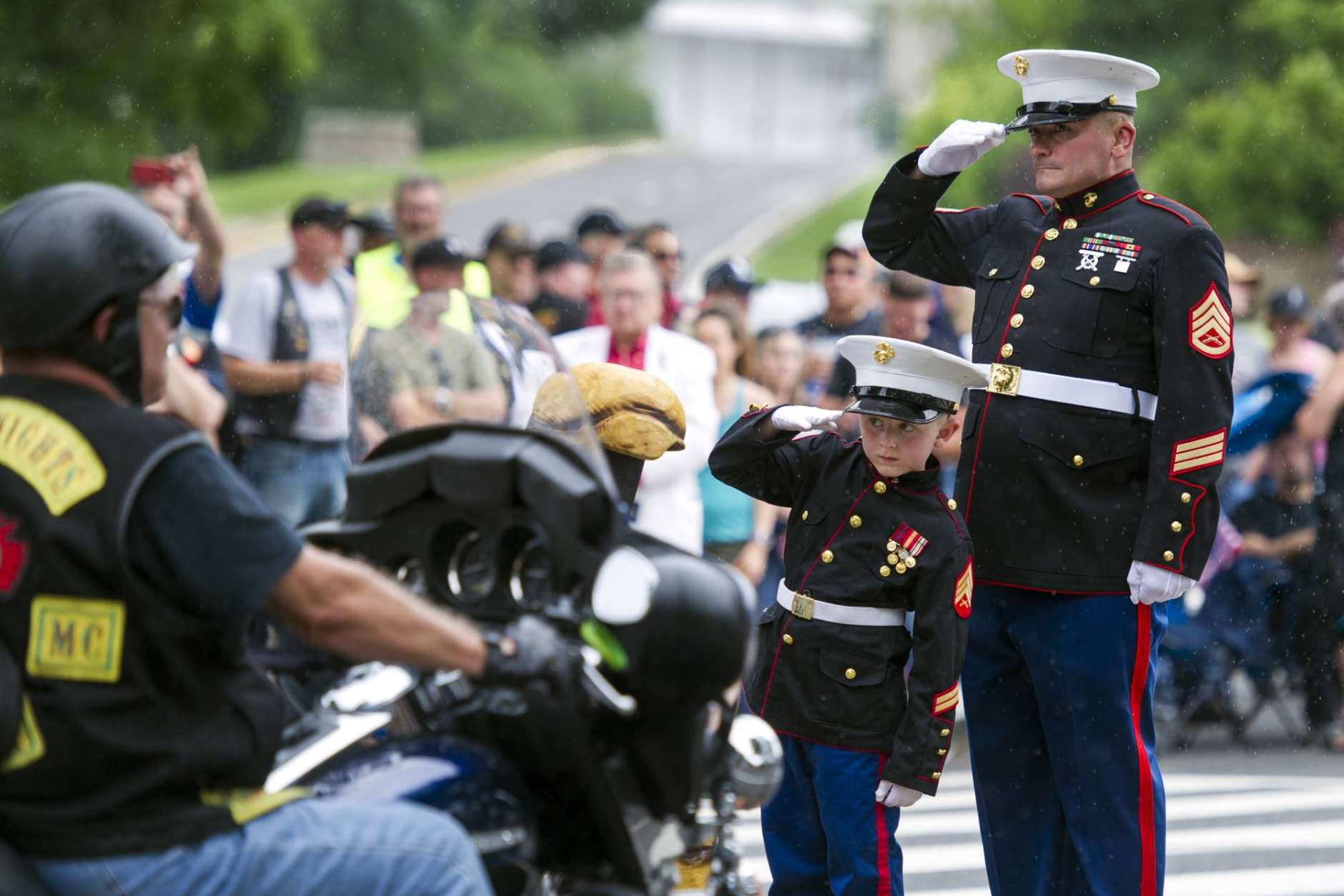 Motorcyclists pass Marine Staff Sgt. Tim Chambers, Ret., and Christian Jacobs, 6, of Hertford, N.C., as they salute during the 30th anniversary of the Rolling Thunder 'Ride for Freedom' demonstration in Washington, Sunday, May 28, 2017. Jacobs father, Marine Sgt. Christopher Jacobs, was killed while serving in 2011. Rolling Thunder seeks to bring full accountability for all U.S. prisoners of war and missing in action (POW/MIA) soldiers. (AP Photo/Cliff Owen)