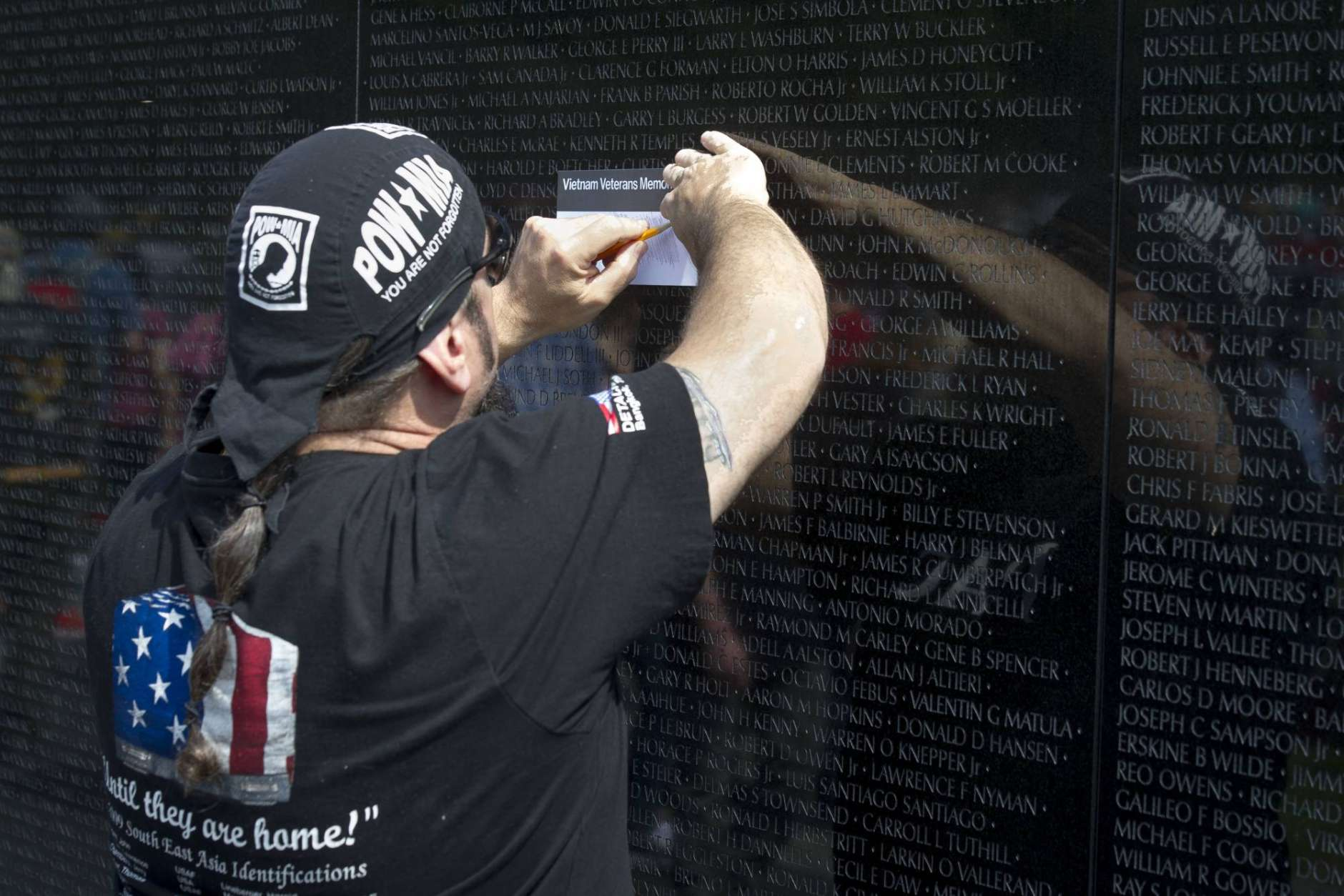 A motorcyclists transfer a name of a deceased soldier at the Vietnam Veterans Memorial during the 30th anniversary of the Rolling Thunder 'Ride for Freedom' demonstration in Washington, Sunday, May 28, 2017. Rolling Thunder seeks to bring full accountability for all U.S. prisoners of war and missing in action (POW/MIA) soldiers. (AP Photo/Cliff Owen)