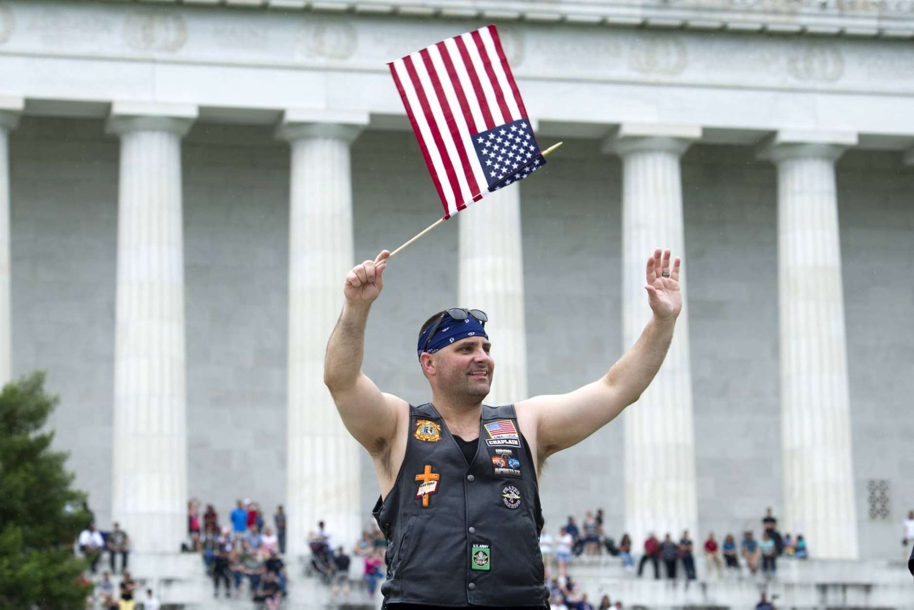 A motorcyclist in front of the Lincoln Memorial, waves to riders as they participate in the 30th anniversary of the Rolling Thunder 'Ride for Freedom' demonstration in Washington, Sunday, May 28, 2017. Rolling Thunder seeks to bring full accountability for all U.S. prisoners of war and missing in action (POW/MIA) soldiers. (AP Photo/Cliff Owen)