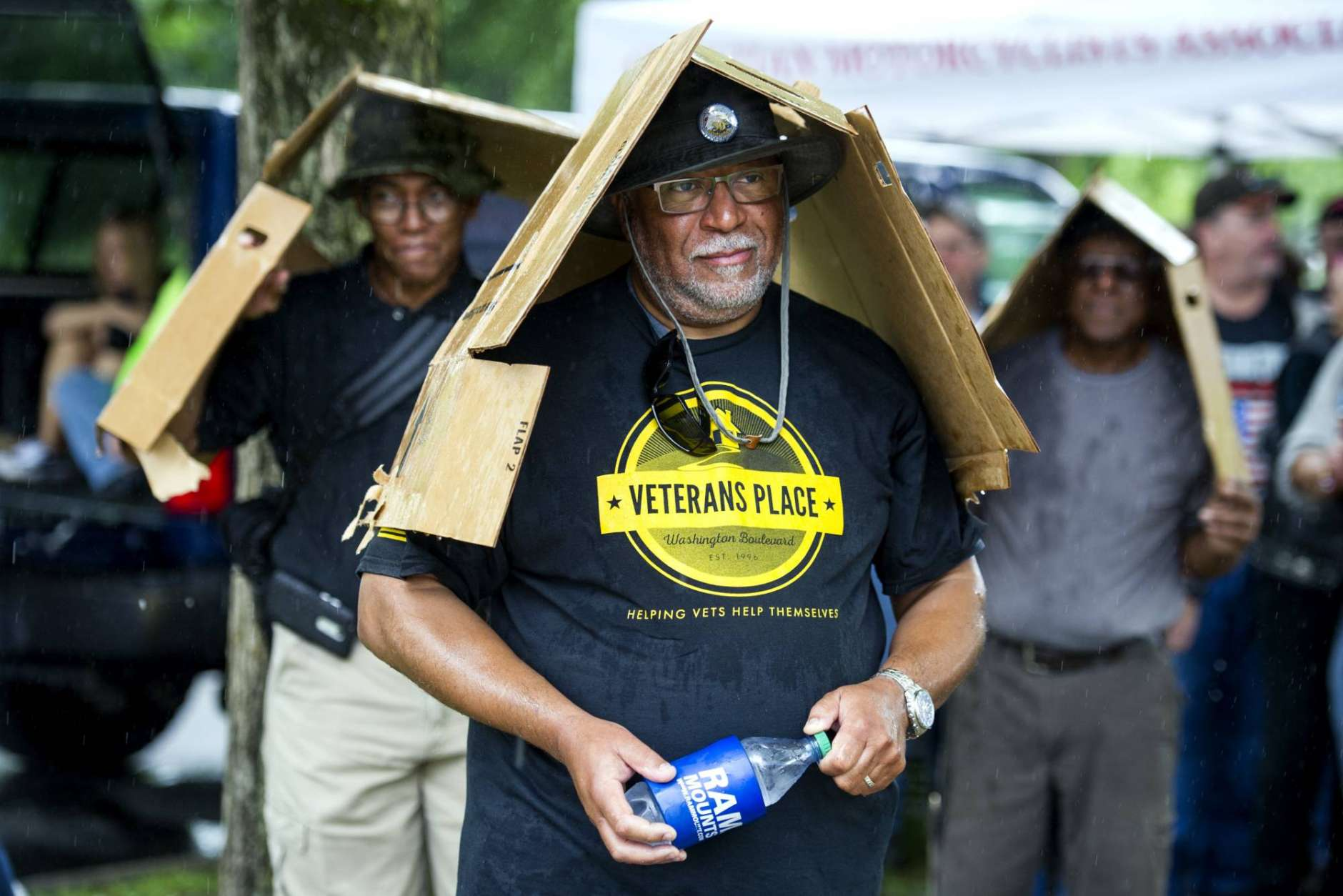 Three men watching motorcyclists, use cardboard boxes as umbrellas while it rains on the 30th anniversary of the Rolling Thunder 'Ride for Freedom' demonstration in Washington, Sunday, May 28, 2017. Rolling Thunder seeks to bring full accountability for all U.S. prisoners of war and missing in action (POW/MIA) soldiers. (AP Photo/Cliff Owen)