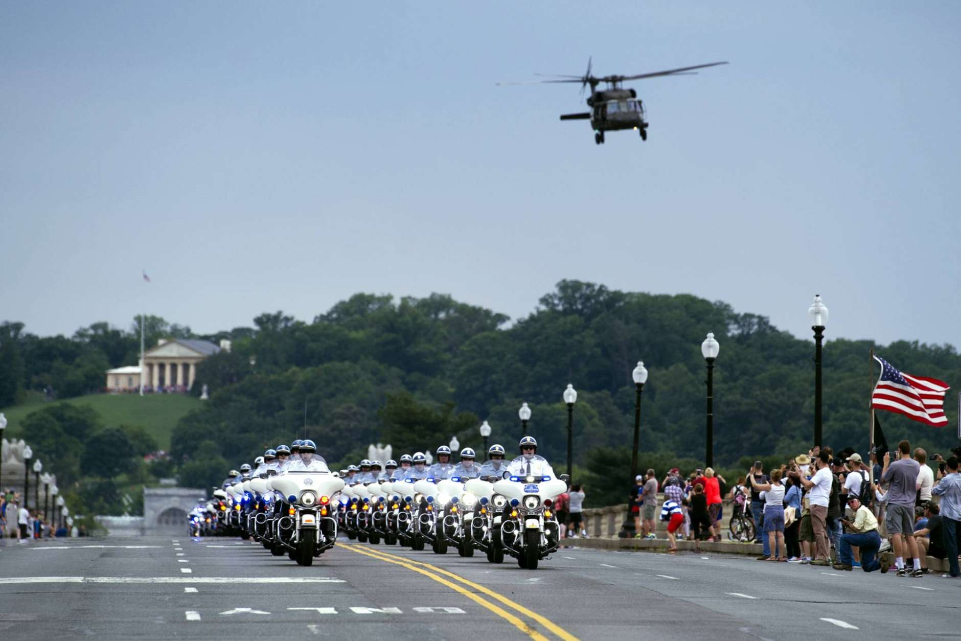 A military helicopter flies over a police escort on the Memorial Bridge, for motorcyclists riding in the 30th anniversary of the Rolling Thunder 'Ride for Freedom' demonstration in Washington, Sunday, May 28, 2017. Rolling Thunder seeks to bring full accountability for all U.S. prisoners of war and missing in action (POW/MIA) soldiers. (AP Photo/Cliff Owen)