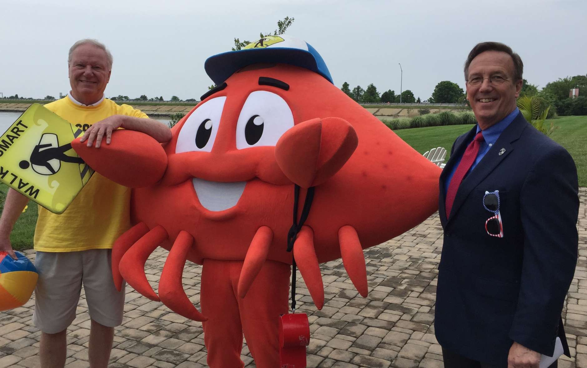 """Ocean City Mayor Rick Meehan and Maryland Deputy Secretary of Transportation, Jim Ports pose with Cheswick, the Lifeguard Crab, who counsels pedestrians and bicyclists to https://oceancitymd.gov/oc/walksmart/ """"Save Yourself!"""""""