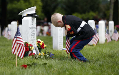 Christian Jacobs, 5, of Hertford, N.C., dressed as a Marine, works to place a flag in front of his father's gravestone on Memorial Day in Section 60 at Arlington National Cemetery in Arlington, Va., Monday, May 30, 2016. Christian's father Marine Sgt. Christopher James Jacobs died in a training accident in 2011. (AP Photo/Carolyn Kaster)