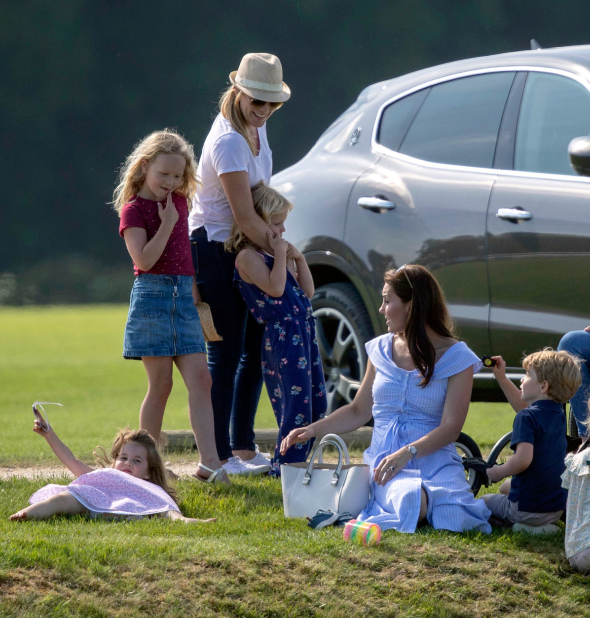 Britain's Kate, the Duchess of Cambridge, second right, sits with Prince George and Princess Charlotte as she talks to Autumn Phillips and her children, Savannah and Isla, as they watch Prince William take part in the Maserati Royal Charity Polo Trophy at the Beaufort Polo Club, in Tetbury, England, Sunday June 10, 2018.