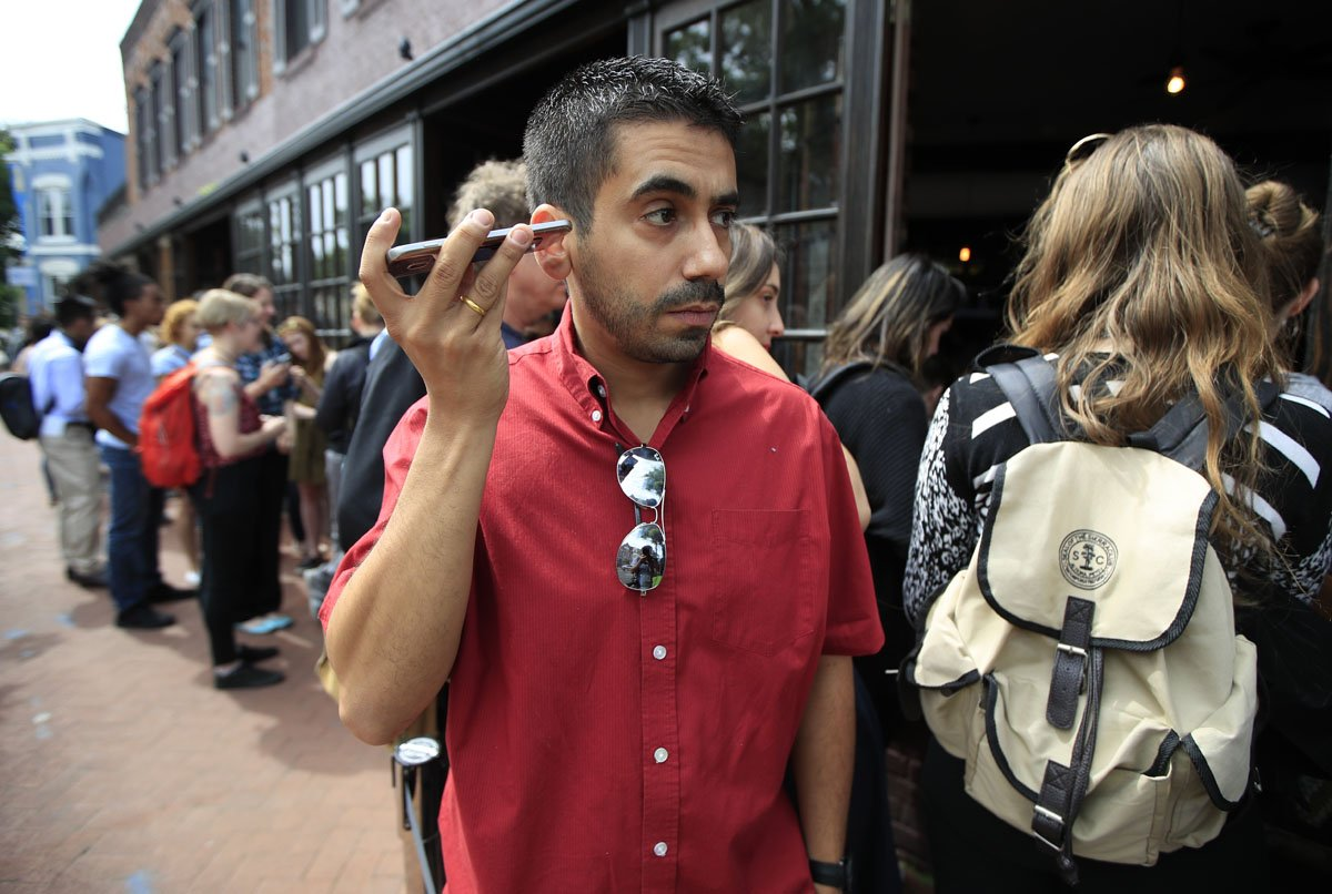 Orlando Lopez of Reston, Va., listens to live broadcast broadcast of former FBI director James Comey testifying before the Senate Select Committee on Intelligence, on Capitol Hill, with a group of other people lined up at Shaw's Tavern in Washington, Thursday, June 8, 2017. (AP Photo/Manuel Balce Ceneta)