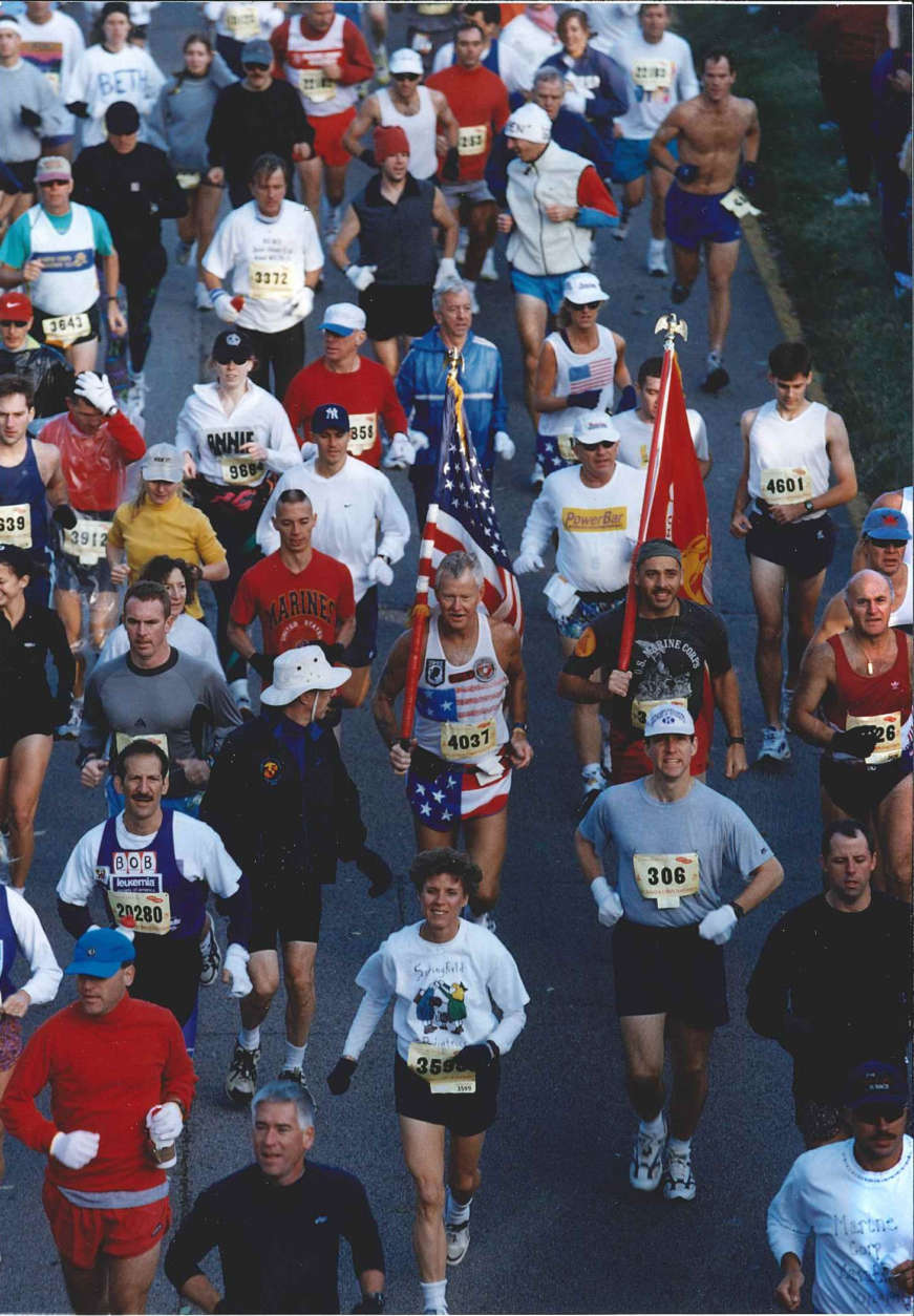 Marine Corps Marathon runners, year not known. Center with flag is Steve Bozeman, a Marine Corps Marathon Hall of Famer. He is among a small group of people recognized for the positive impact they have had in the success of the marathon. (Courtesy Marine Corps Marathon)