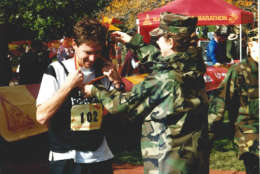 A Marine presents a medal to at finish at the 1999 Marine Corps Marathon. (Courtesy Marine Corps Marathon)