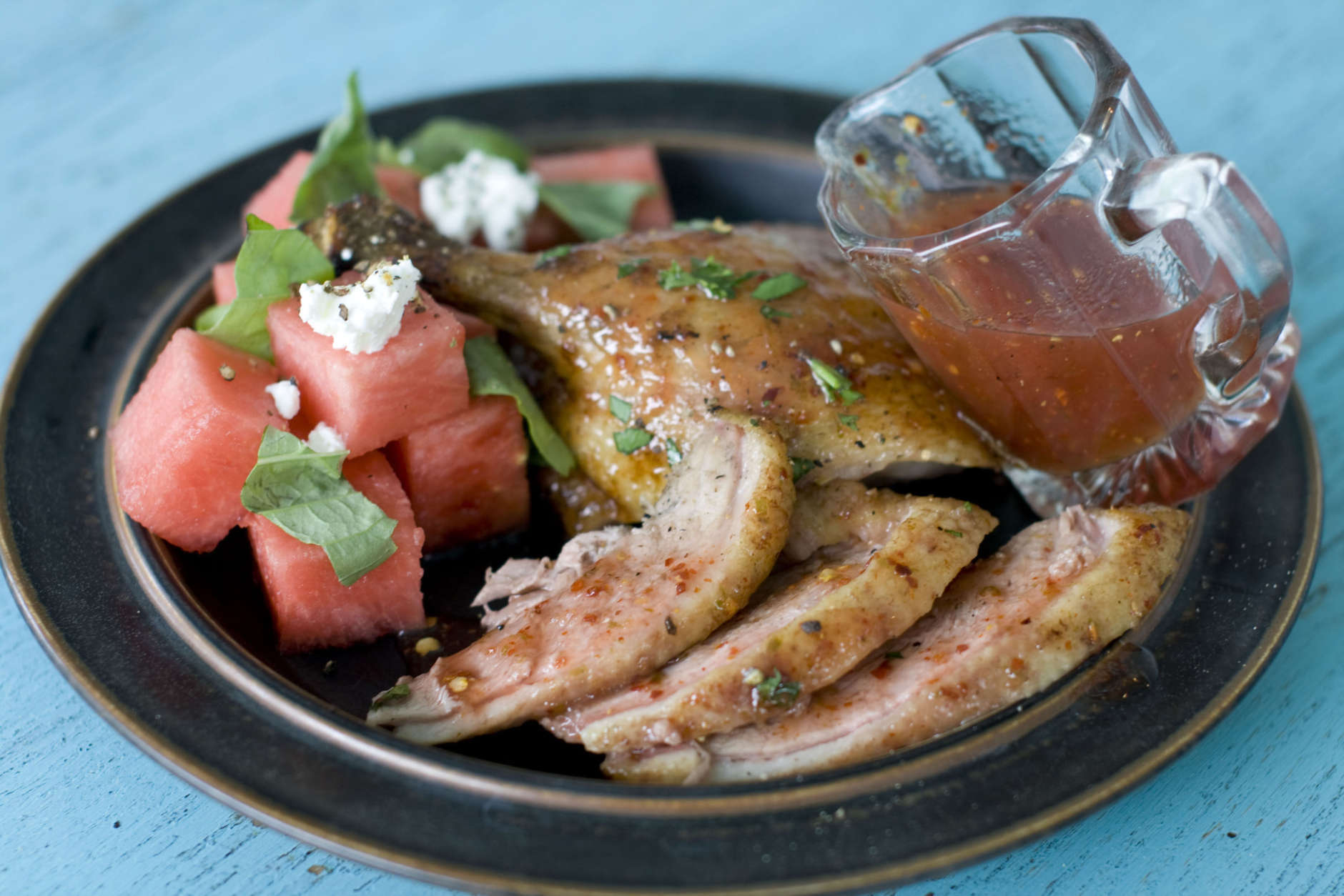In this image taken on May 30, 2012, Elizabeth Karmel's grilled butterflied duck with spicy watermelon glaze is shown on a plate in Concord, N.H. (AP Photo/Matthew Mead)