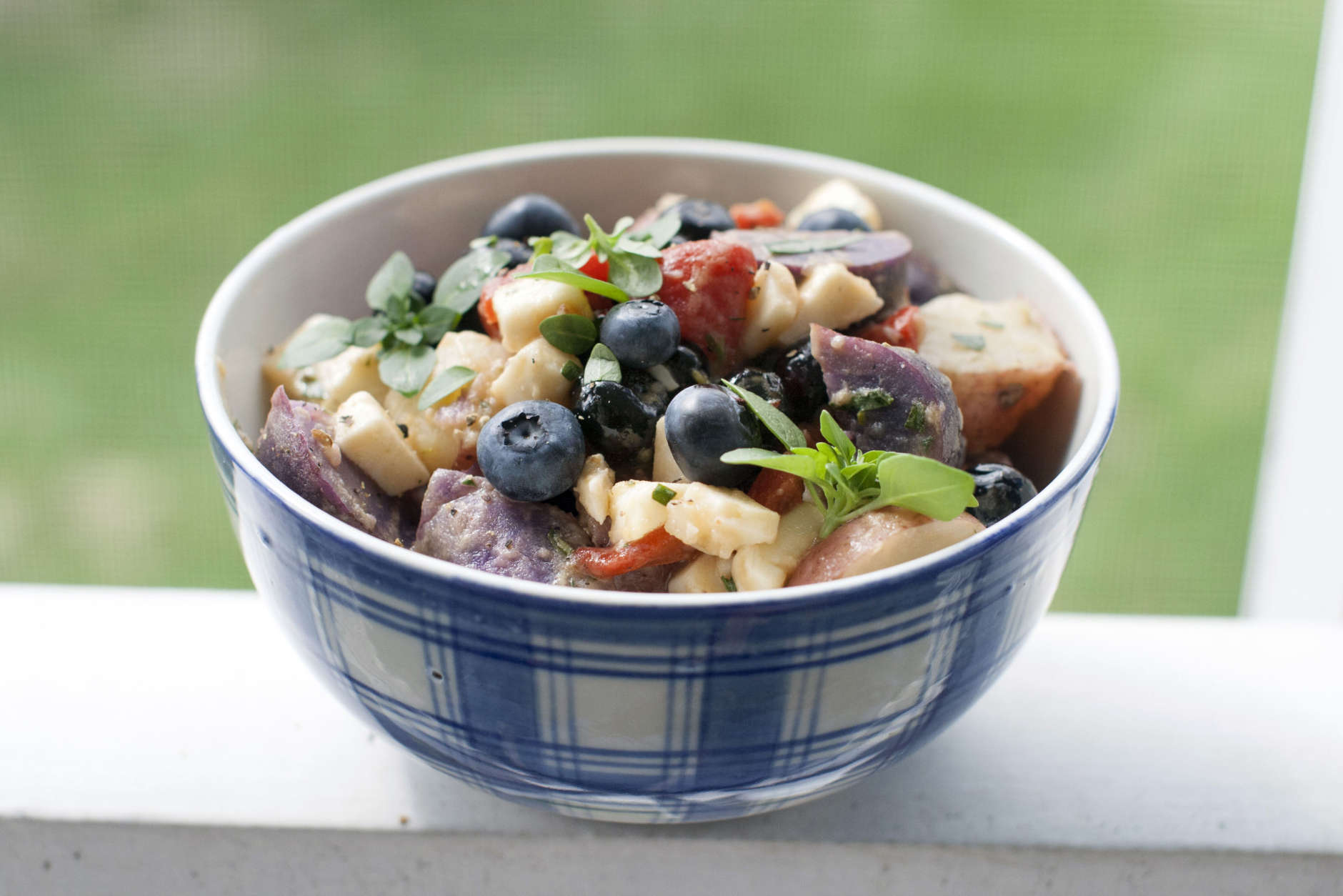 This May 5, 2014 photo shows red, white and blue potato salad in Concord, N.H. Red and purple potatoes, roasted red peppers, cubes of white goat cheese, and several cups of blueberries provide patriotic colors that reflect the spirit of the Fourth of July holiday.  (AP Photo/Matthew Mead)
