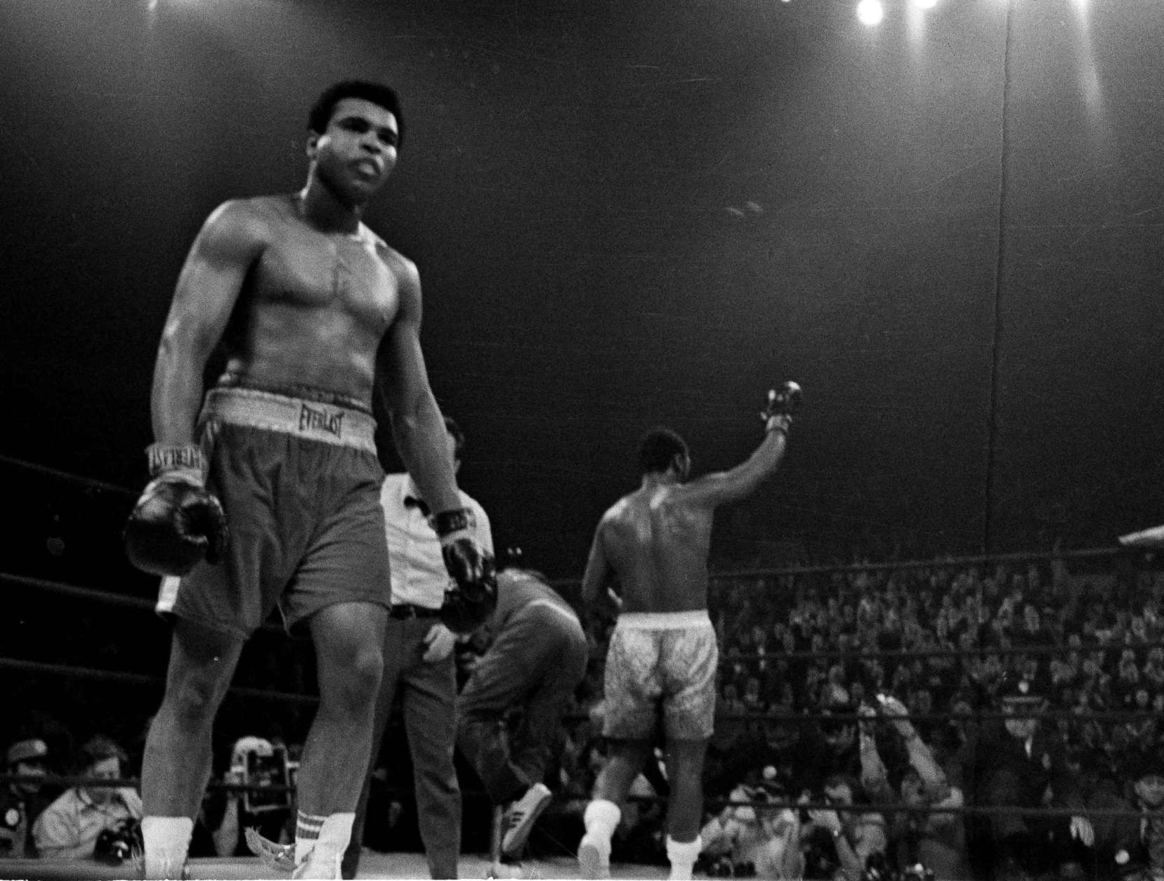 A battered Muhammad Ali walks back to his corner as a triumphant Joe Frazier, background, celebrates his title defense after the 15th round of their title bout in New York, March 8, 1971.  After the bout, Ali was taken to have his injured jaw X-rayed.  (AP Photo)