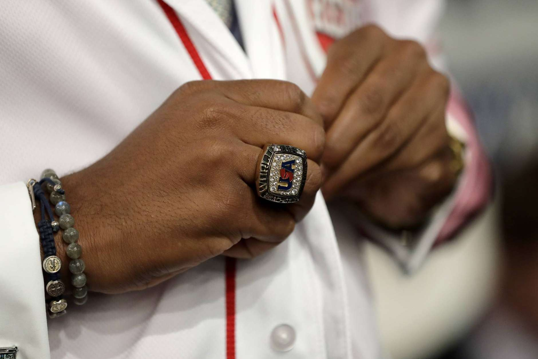 Hunter Greene, a pitcher and shortstop from Notre Dame High School in Sherman Oaks, Calif., buttons on a Cincinnati Reds jersey after being selected No. 2 by the Reds in the first round of the Major League Baseball draft, Monday, June 12, 2017, in Secaucus, N.J. (AP Photo/Julio Cortez)