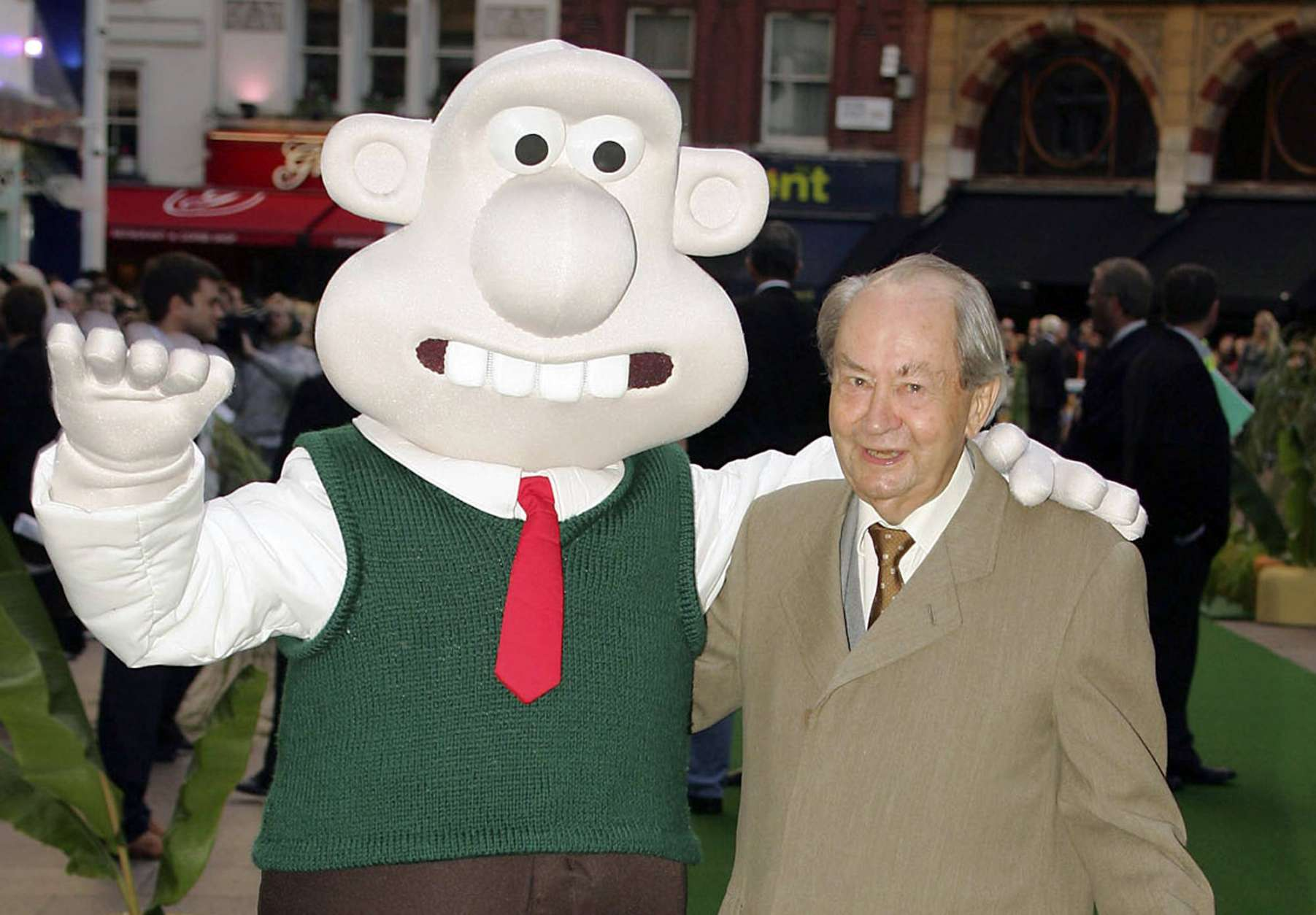 """FILE - In this Sunday, Oct. 2, 2005 file photo, British actor Peter Sallis, who voices the part of Wallace poses with a person dressed as the character 'Wallace' on arrival at the Leicester Square Odeon, London for the premiere of Wallace & Grommit: The Curse of the Were-Rabbit. Sallis, who played irrepressible, cheese-loving inventor Wallace in the """"Wallace and Gromit"""" cartoons, has died. He was 96. Sallis' agents, Jonathan Altaras Associates, say he died Friday, June 2, 2017 in London. (AP Photo/Paul Ashby, File)"""