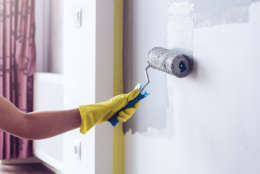 Hand in a yellow protective glove painting a wall in apartment in gray colour with a roller brush.