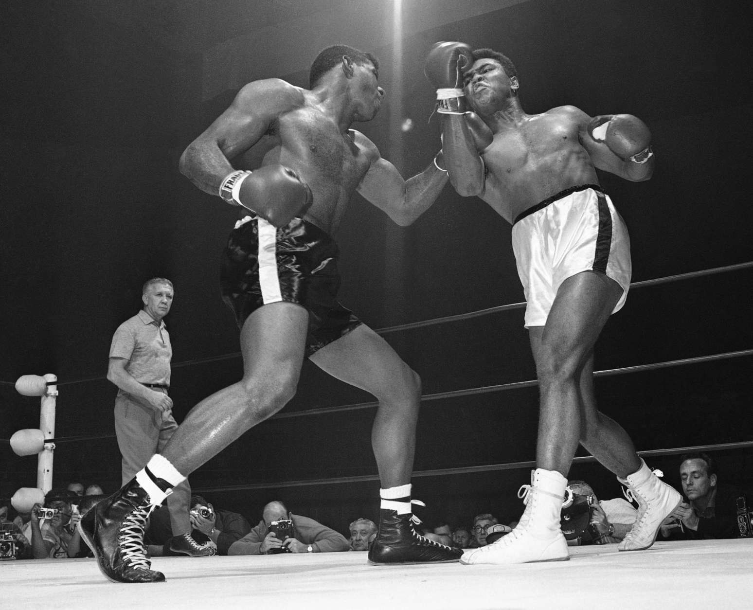 FIULE - In this Nov. 22, 1965, file photo, challenger Floyd Paterson, left, delivers a left hook to the chin of champion Muhammad Ali during the second round of their heavyweight title fight in Las Vegas. Among the questions Jonathan Eig wanted to answer in his upcoming biography of Ali was this: How many punches did Ali take during a career that ended with him devastated by Parkinson's? You'll have to wait until the book comes out to find out, though Ali himself once calculated the figure at 29,000. (AP Photo, File)