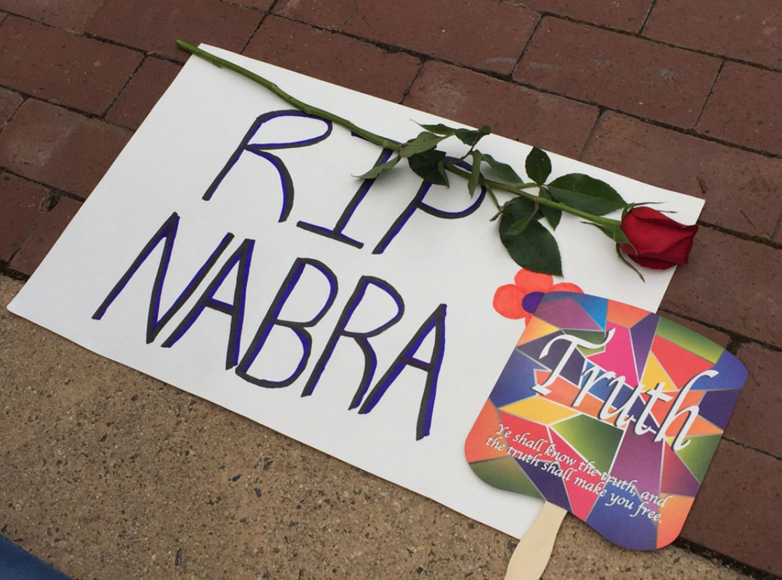 photo shows a sign that says RIP Nabra with a rose