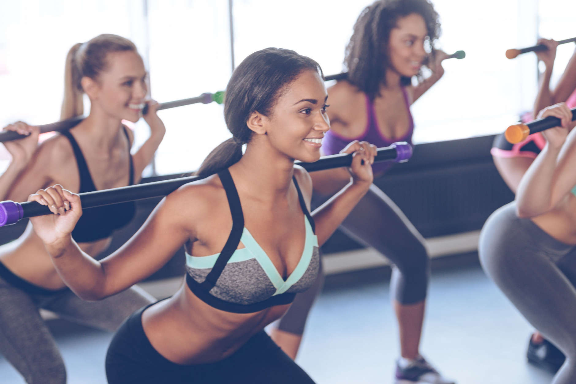 Beautiful young women with perfect bodies in sportswear exercising with barre while standing in front of window at gym