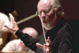 """FILE - In this Tuesday, May 18, 2004 file photo composer John Williams leads the Boston Pops orchestra during a rehearsal in Boston. Williams, an Oscar- and Grammy-winning composer, who wrote the score for """"Star Wars: The Force Awakens,"""" will help Pops conductor Keith Lockhart lead a performance of selections from the hit movie's soundtrack as part of the orchestra's spring concert schedule. (AP Photo/ Robert E. Klein, File)"""