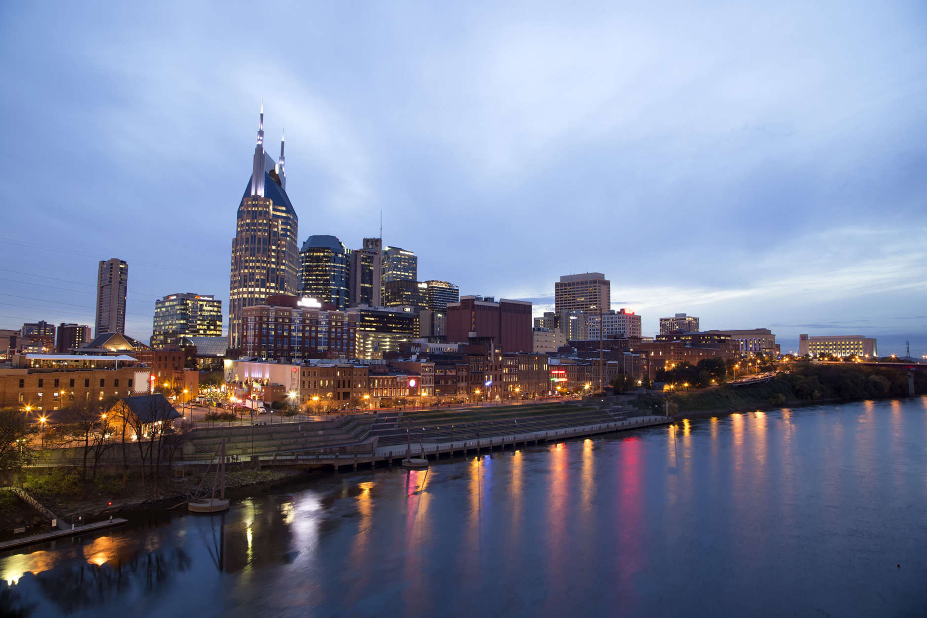 Nashville Skyline at sunset with reflections in river.  An Autumn afternoon with a colorful blue sky at twilight and the city lights all lit up. (Thinkstock)