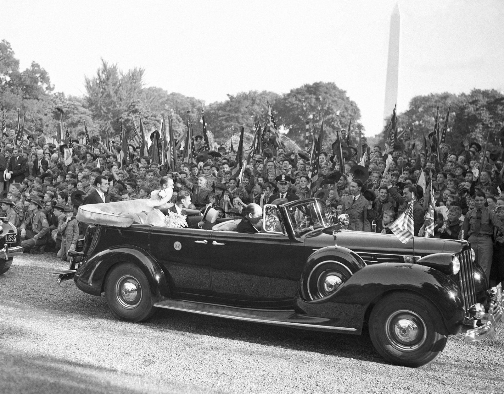 Throng of Boy Scouts cheered the King and Queen of England when the foreign royalty reviewed the scouts at the White House in Washington, D.C., on June 8, 1939. The king and queen are in back of car driving by the waving youths. (AP Photo)