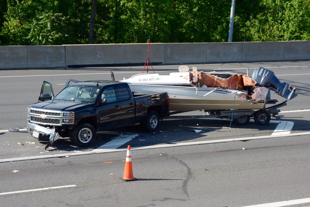 Two people got out of the truck in order to re-secure the boat when a tractor-trailer drifted into the median, hitting the boat and one of the pedestrians. (WTOP/Dave Dildine)