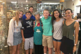 """Sun Pacylowski's husband John a few months after the deluge after he fell from a ladder while making flood-related repairs to the couple's Main Street shop """"Precious Gifts."""" Pacylowski (center) ran the store for 27 years with her husband. The gift shop reopened earlier this month. (WTOP/Mike Murillo)"""