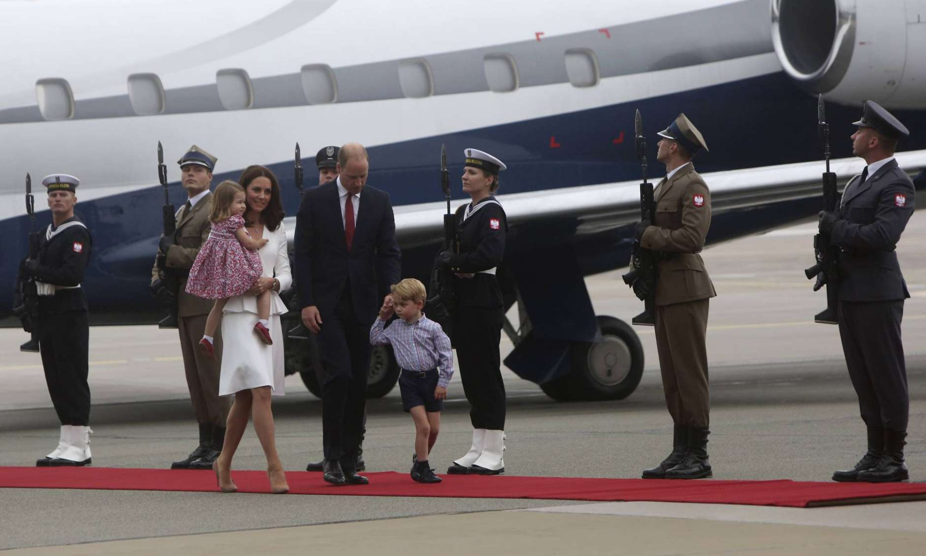 Britain's Kate, the Duchess of Cambridge holding Princess Charlotte, Prince William and Prince George walk past the honor guard, during the arrival ceremony, in Warsaw , Poland, Monday, July 17, 2017. The Duke and Duchess of Cambridge and their children have arrived in Poland, the first leg of a goodwill trip to two European Union nations that seeks to underscore Britain's friendly ties despite its negotiations to leave the bloc. (AP Photo/Czarek Sokolowski)
