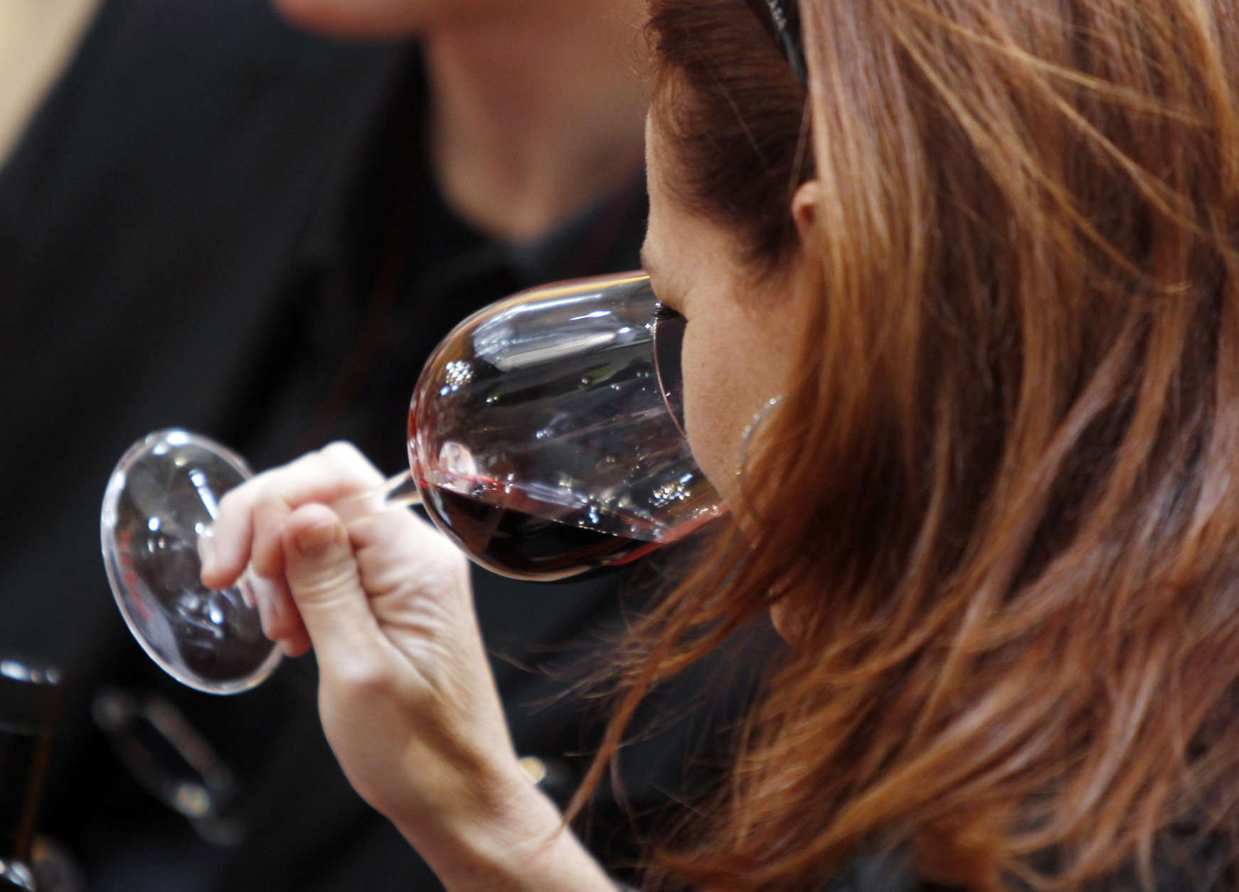 """A woman tastes a glass of Tuscan red wine on the opening day of the 44th edition of the annual International Wine and Spirits Exhibition """"Vinitaly"""", in Verona, northern Italy, Thursday, April 8, 2010. The wine exhibition runs until April 12. (AP Photo/Luca Bruno)"""