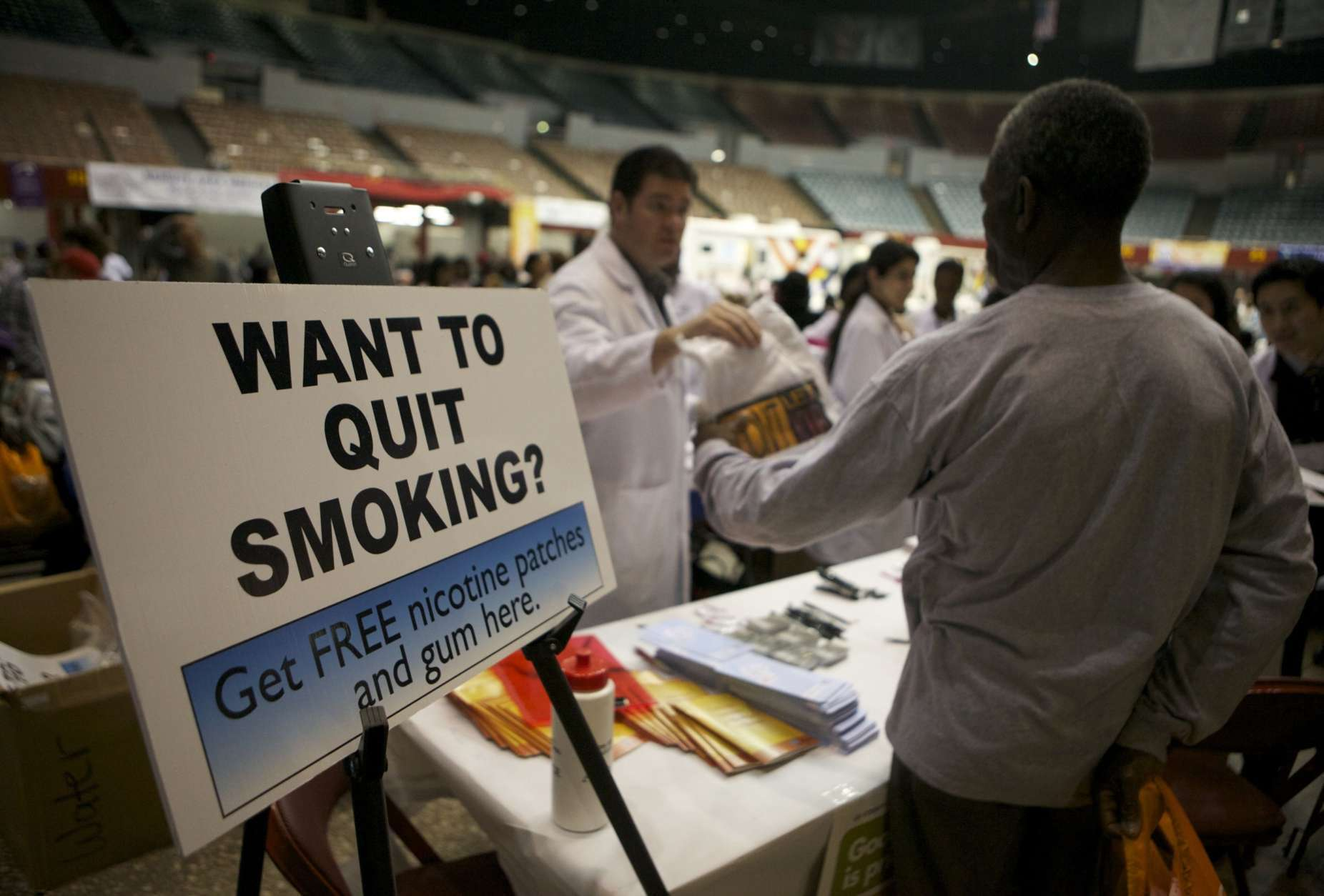 Smokers without medical insurance receive free nicotine patches and gum at the Remote Area Medical (RAM) clinic inside the Los Angeles Sports Arena in Los Angeles on Tuesday, April 27, 2010. The free health clinic opened its doors Tuesday to thousands of patients clamoring for dental, vision and medical care. Patients registered in advance to see doctors at the event, which is being run by the Tennessee-based nonprofit group Remote Area Medical. The clinic expects to serve about 1,200 patients a day. (AP Photo/Damian Dovarganes)
