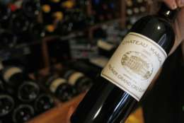 In this Sept. 20 2012, photo, a wine seller presents a 2005 bottle of Bordeaux wine Chateau Margaux at his shop in Paris. The United States wants to sell some of their wines in the European Union with a ''chateau'' label.  Next week, EU experts will look whether it should permitted with a fight among member states set for later this year, well after the wine harvest. (AP Photo/Remy de la Mauviniere)