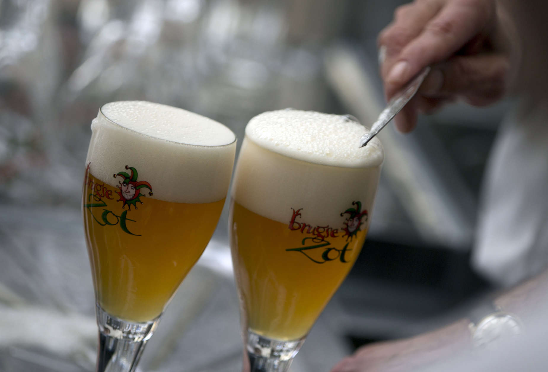 A workers scrapes the foam off of a glass of Brugse Zot beer before serving it at the Halve Maan Brewery in Bruges, Belgium on Thursday, May 26, 2016. The brewery has recently created a beer pipeline which will ship beer straight from the brewery to the bottling plant, two kilometers away, through underground pipes running between the two sources. (AP Photo/Virginia Mayo)
