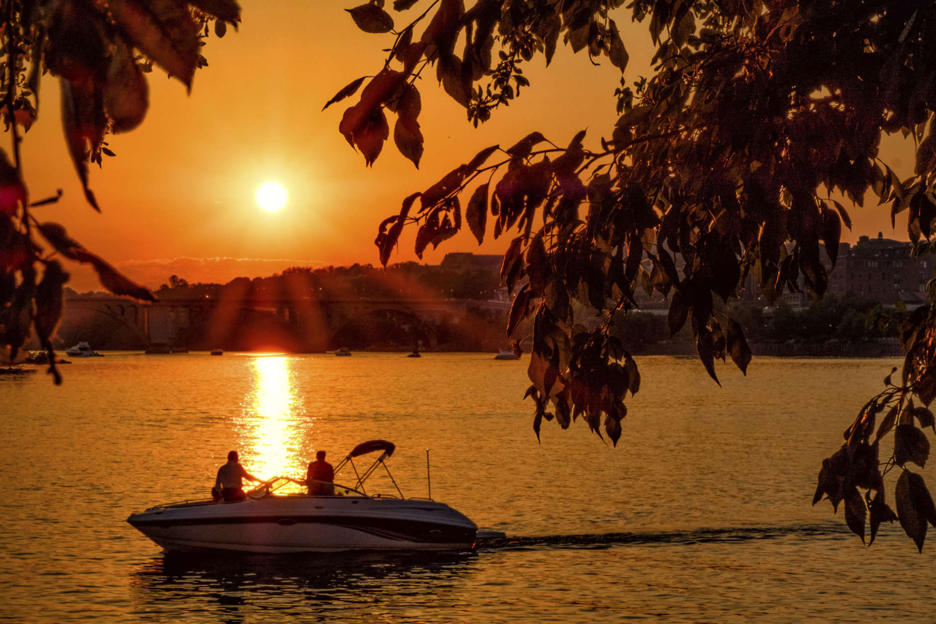 Recreational boaters watch the sunset on the Potomac River near the Francis Scott Key Bridge in Washington, Sunday, June 11, 2017. Temperatures in the nation's capital reached the mid-90s Sunday. (AP Photo/J. David Ake)