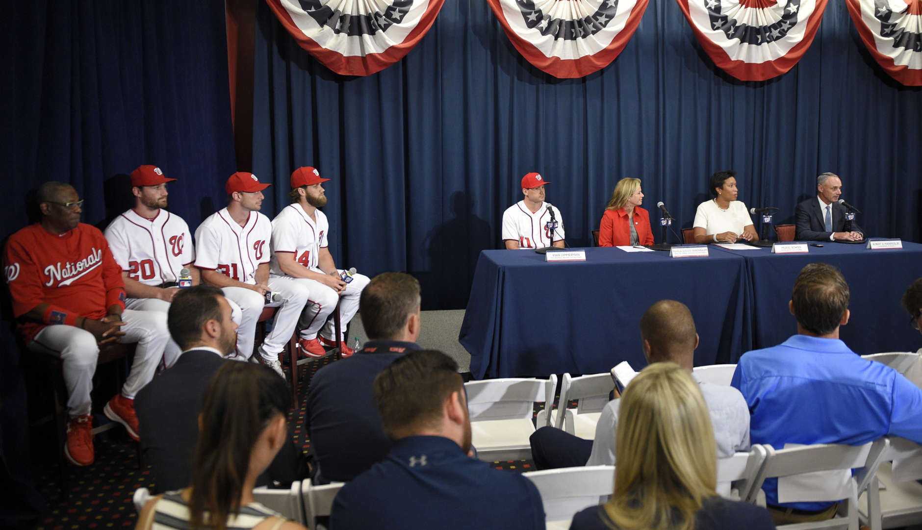 From right to left, Rob Manfred, Commissioner of Baseball, Muriel Bowser, Mayor of the District of Columbia; Marla Lerner Tanenbaum, Washington Nationals' Ryan Zimmerman, Bryce Harper, Max Scherzer, Daniel Murphy, and manager Dusty Baker during a baseball press conference to unveil the 2018 MLB All-Star Game logo, Wednesday, July 26, 2017, in Washington. (AP Photo/Nick Wass)