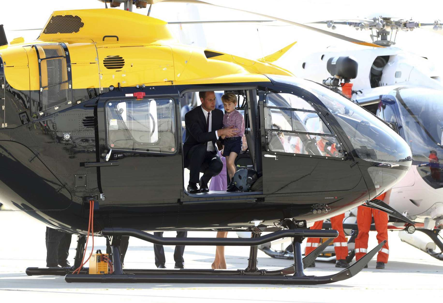 Britain's Prince William looks at the interior of an Airbus helicopter with his son Prince George in Hamburg, Germany,  Friday, July 21, 2017.  (Christian Charisius/dpa via AP)