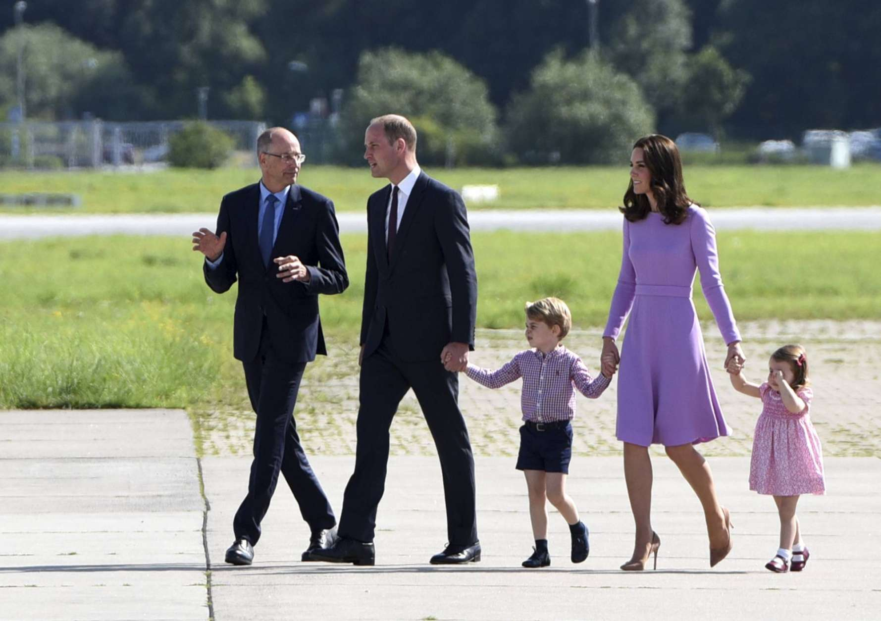 Britain's Prince William, second left, and his wife Kate, the Duchess of Cambridge, second right, together with their children, Prince George, center, and Princess Charlotte, right, visit the helicopter branch of Airbus in Hamburg, Friday, July 21, 2017. At left Wolfgang Schoder,  CEO Airbus Helicopters. (Daniel Bockwoldt/Pool Photo via AP)