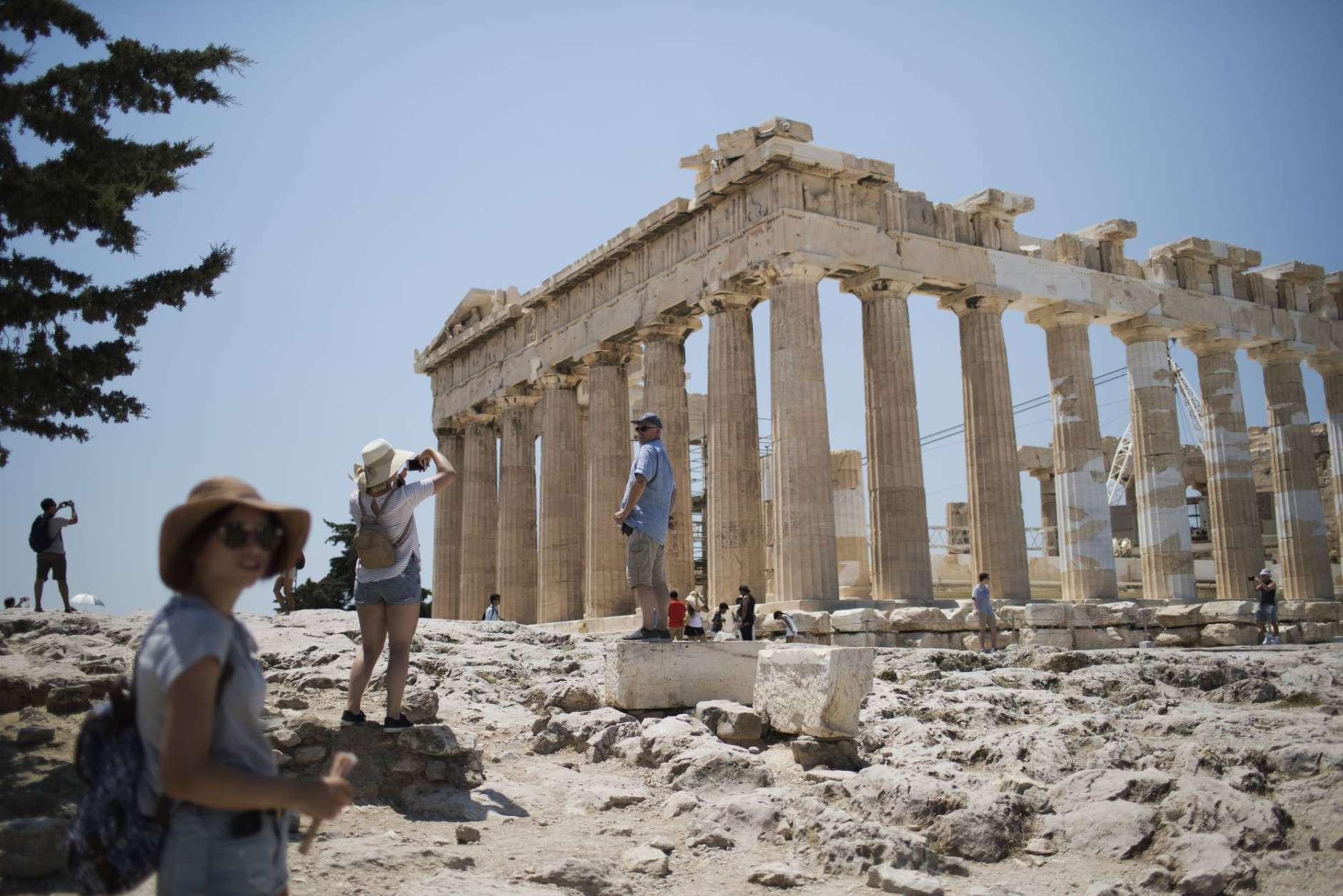 Tourists take pictures in front of the fifth century BC Parthenon temple at the Acropolis hill in Athens, Wednesday, July 12, 2017. Greece's Culture Ministry says that all Greek archaeological sites, including Athens' internationally famed Acropolis, will close during the hottest hours of the day from Wednesday, due to a predicted heat wave. (AP Photo/Petros Giannakouris)