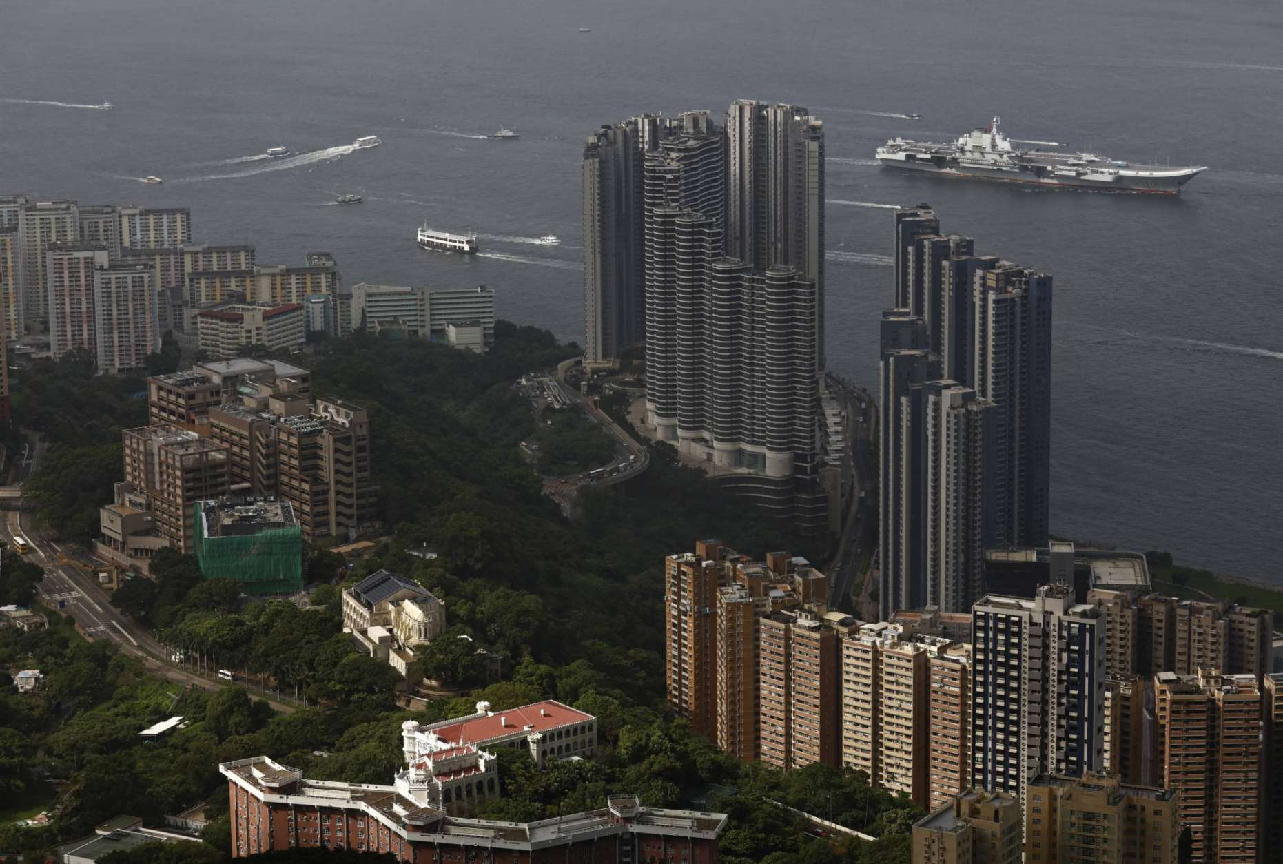 The Liaoning, China's first aircraft carrier, right top, sails into Hong Kong for a port call, Friday, July 7, 2017, to celebrate the 20th anniversary of the People's Liberation Army (PLA) garrison's presence in the semi-autonomous Chinese city and former British colony. (AP Photo/Vincent Yu)