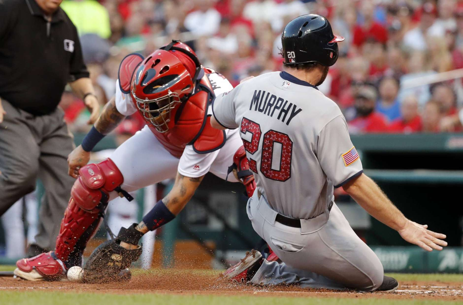 Washington Nationals' Daniel Murphy (20) scores as the throw gets away from St. Louis Cardinals catcher Yadier Molina during the third inning of a baseball game, Sunday, July 2, 2017, in St. Louis. (AP Photo/Jeff Roberson)