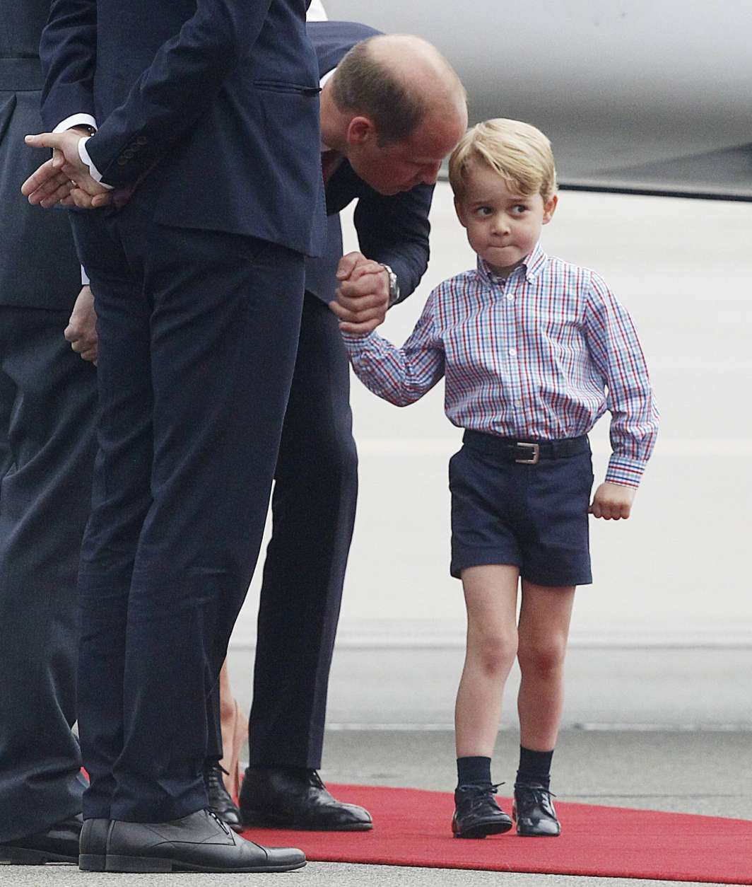 Britain's Prince William, left, holds the hand of his son Prince George on arrival at the airport, in Warsaw, Poland, Monday, July 17, 2017. The Duke and Duchess of Cambridge and their children have arrived in Poland, the first leg of a goodwill trip to two European Union nations that seeks to underscore Britain's friendly ties despite its negotiations to leave the bloc. (AP Photo/Czarek Sokolowski)