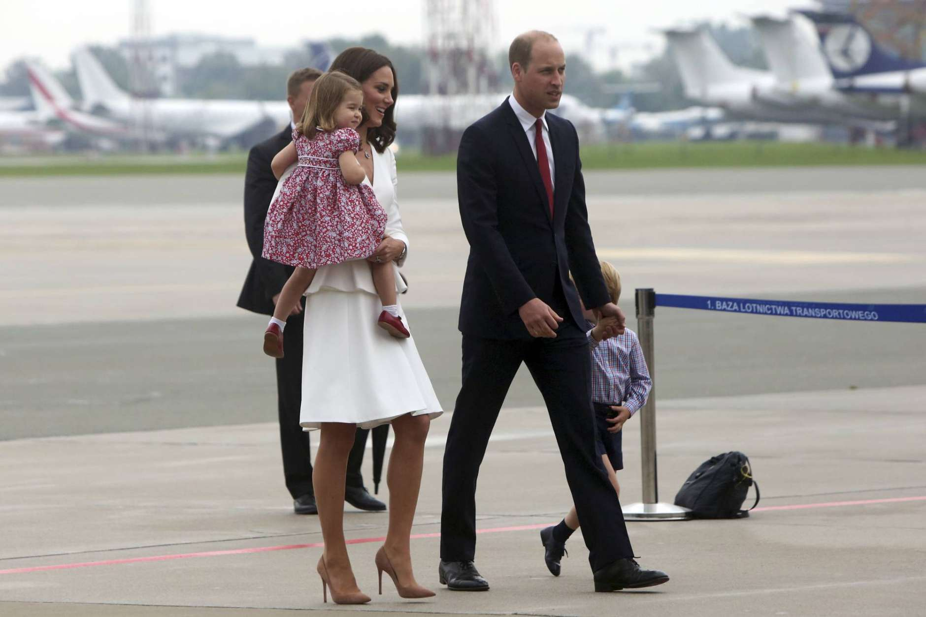 Britain's Kate, the Duchess of Cambridge holding Princess Charlotte walks with Prince William and Prince George towards the airport upon arrival, in Warsaw , Poland, Monday, July 17, 2017. The Duke and Duchess of Cambridge and their children have arrived in Poland, the first leg of a goodwill trip to two European Union nations that seeks to underscore Britain's friendly ties despite its negotiations to leave the bloc. (AP Photo/Czarek Sokolowski)