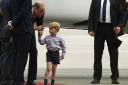 Britain's Prince William, second left, holds the hand of his son Prince George on arrival at the airport, in Warsaw, Poland, Monday, July 17, 2017. The Duke and Duchess of Cambridge and their children have arrived in Poland, the first leg of a goodwill trip to two European Union nations that seeks to underscore Britain's friendly ties despite its negotiations to leave the bloc. (AP Photo/Czarek Sokolowski)