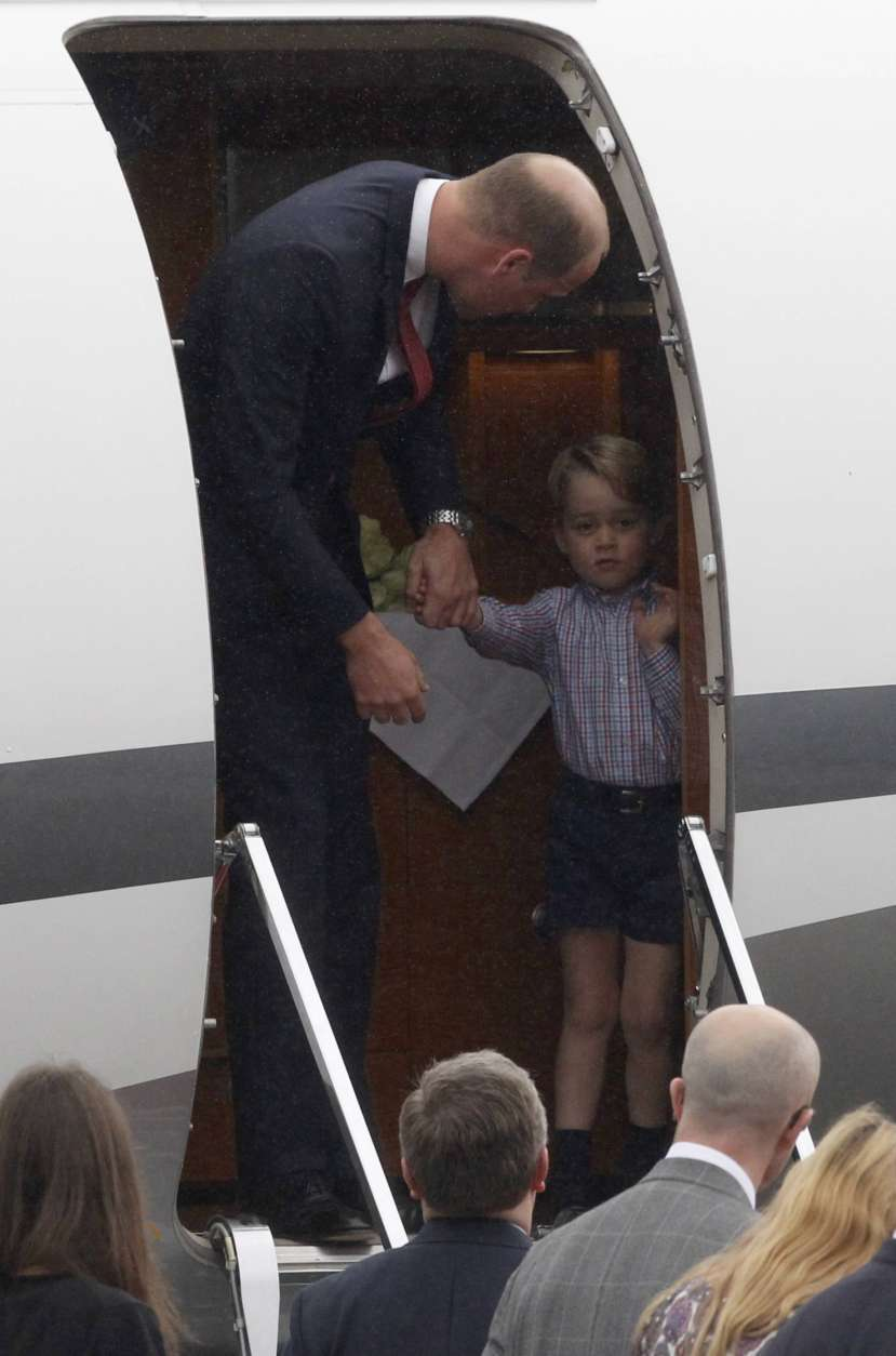 Britain's Prince William, left, disembarks the plane with Prince George, on arrival, in Warsaw, Poland, Monday, July 17, 2017. The Duke and Duchess of Cambridge and their children have arrived in Poland, the first leg of a goodwill trip to two European Union nations that seeks to underscore Britain's friendly ties despite its negotiations to leave the bloc. (AP Photo/Czarek Sokolowski)