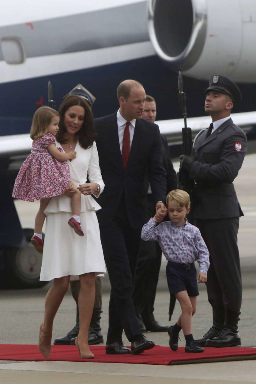 Britain's Kate, the Duchess of Cambridge holding Princess Charlotte walks with Prince William and Prince George as they arrive at the airport, in Warsaw , Poland, Monday, July 17, 2017. The Duke and Duchess of Cambridge and their children have arrived in Poland, the first leg of a goodwill trip to two European Union nations that seeks to underscore Britain's friendly ties despite its negotiations to leave the bloc. (AP Photo/Czarek Sokolowski)