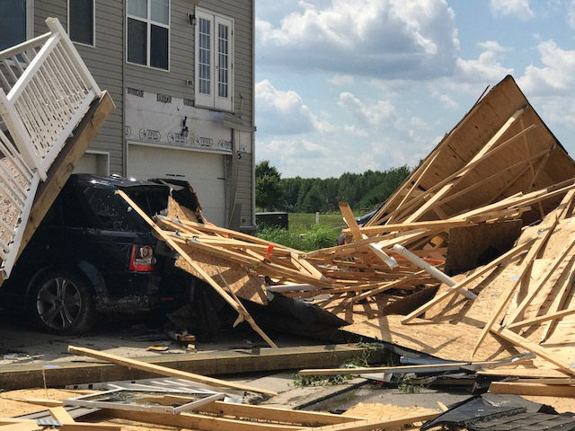 A truck lies buried beneath pieces of roofing and the remnants of a porch in Stevensville, Maryland on Monday, July 24, 2017. Federal officials surveyed damage from the overnight storm to determine if a tornado was the cause. (WTOP/Steve Dresner)