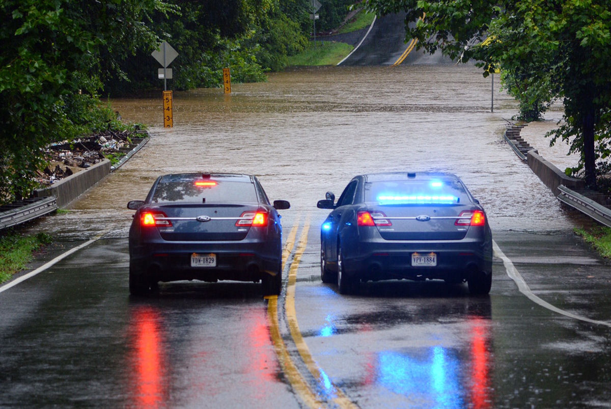 Police in Annadale, Virginia, block off Woodburn Road at Accotink Creek that is covered with more than two feet of water. (WTOP/Dave Dildine)