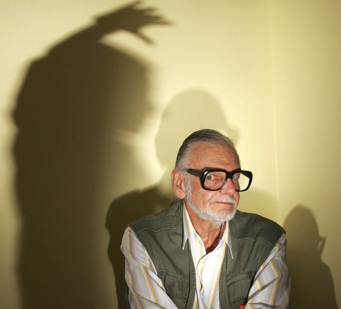 """George Romero, whose classic ``Night of the Living Dead'' and other horror films turned zombie movies into social commentaries and who saw his flesh-devouring undead spawn countless imitators, remakes and homages, has died. He was 77. Romero, director of """"Night of the Living Dead,"""" """"Dawn of the Dead,"""" Day of the Dead,"""" and his latest film """"Land of the Dead,"""" poses with shadows June 16, 2005, in Beverly Hills, Calif. (AP Photo/Chris Carlson)"""